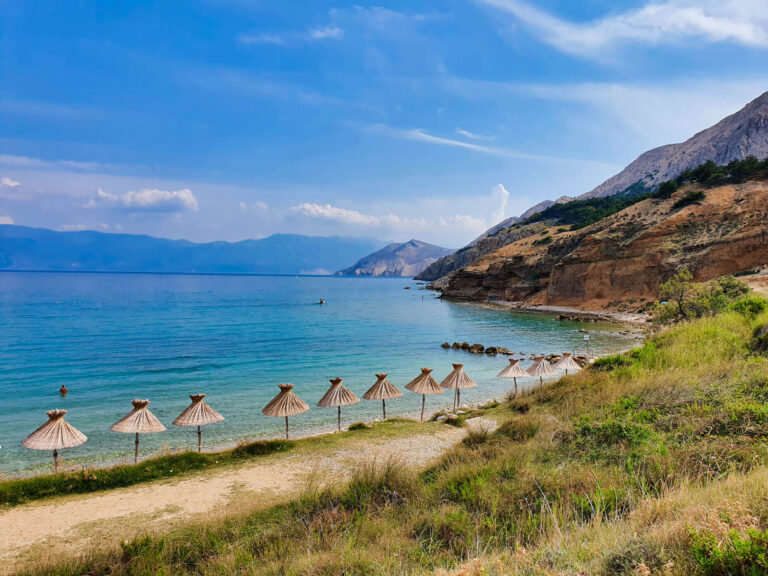 Umbrellas along the shore on Vela Plaža Baška beach