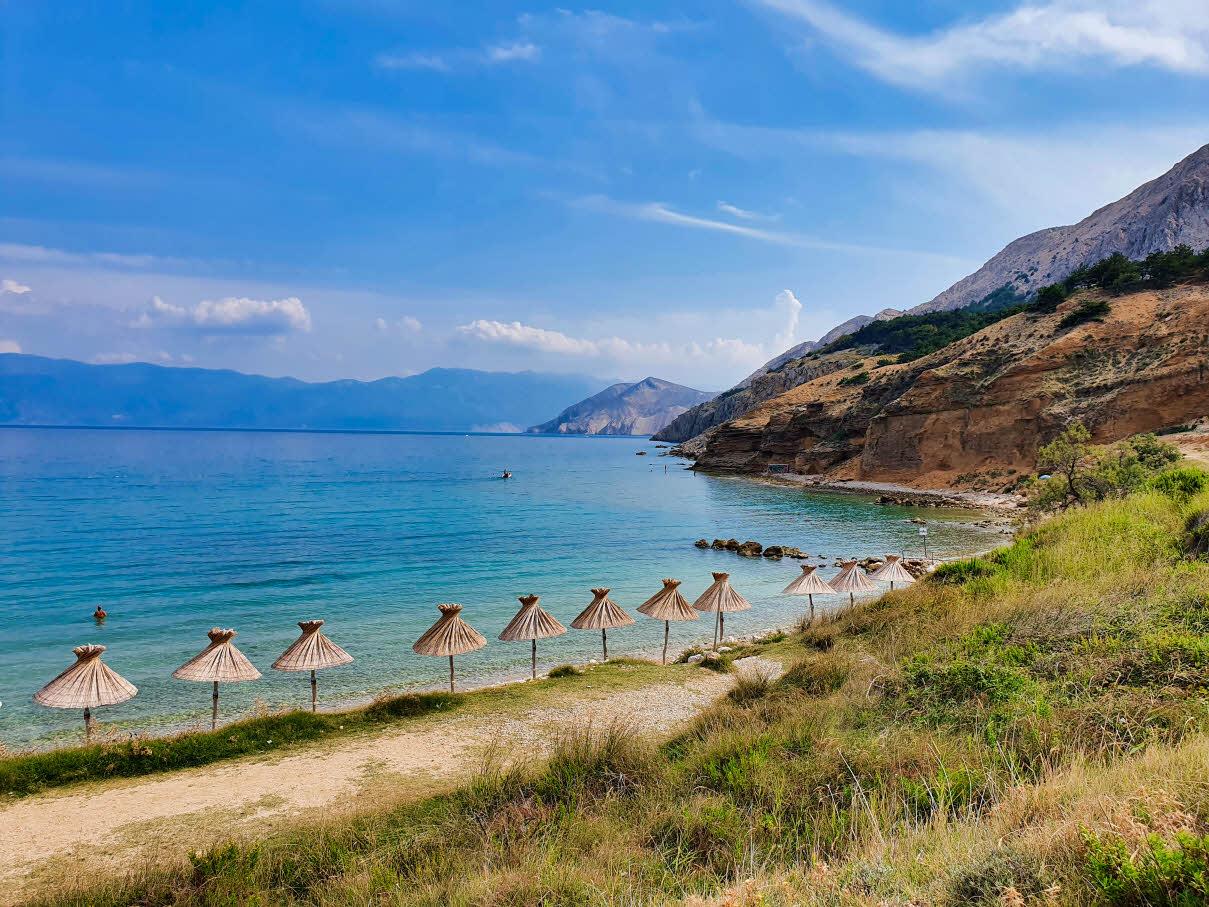 Umbrellas along the shore on Vela Plaža Baška beach