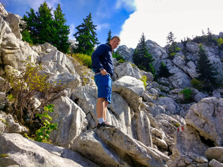 Climbing over rocks to the top of the mountain Balinovac